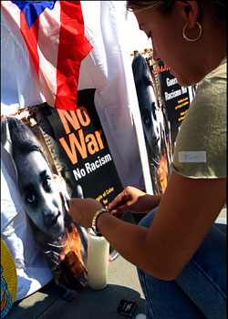 woman places flowers near a no war no racism poster